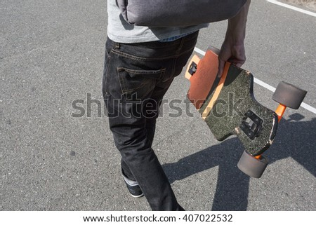 man carries a longboard. The boy goes on the asphalted road holding a longboard - stock photo