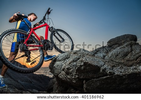 Man carrying a bike on the rock during sunset