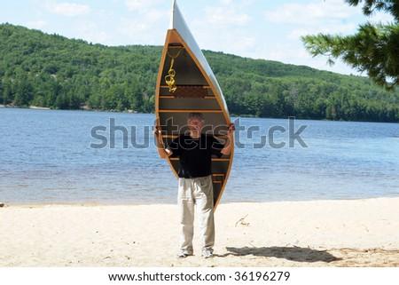 Man carrying a canoe - stock photo