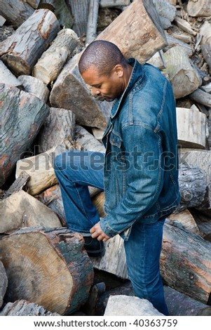 man carrying a log on his shoulder through a woodpile