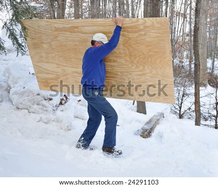 Man carrying a sheet of plywood through the snow - stock photo