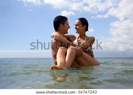 Man carrying a woman in his arms in the sea