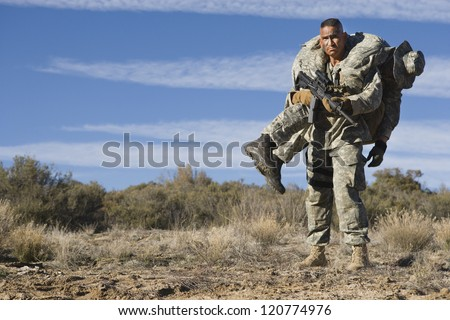 Man carrying an injured solider on shoulder - stock photo