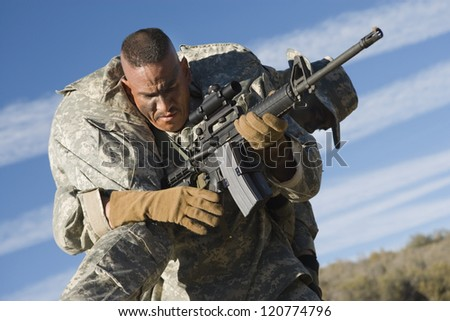 Man carrying an injured solider on shoulder on mission - stock photo