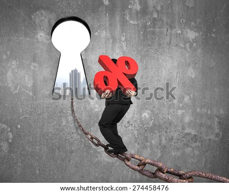 Man carrying 3D red percentage sign walking on old iron chain toward keyhole door, with urban scene view and gray concrete wall background - stock photo