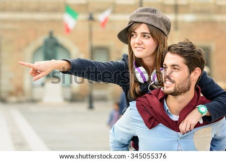 Man carrying girl in piggyback his girlfriend during shopping in town. Couple having fun discover a sunny destination city. Picture of young joyful couple travel and discovery, smart lifestyle. - stock photo