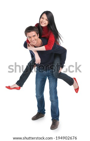 Man carrying girlfriend on his back. happy couple playing on white background - stock photo