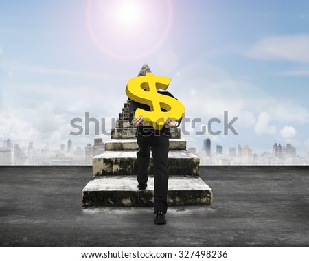 Man carrying golden dollar sign climbing old concrete stairs, with sunny sky background. - stock photo