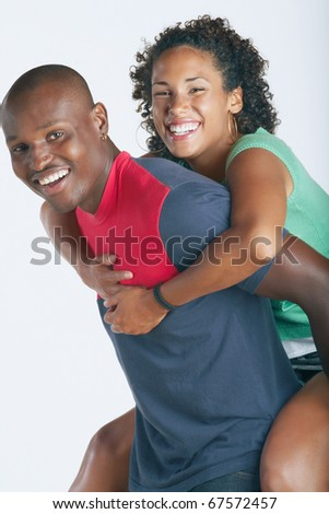 Man carrying his girlfriend on his back - stock photo