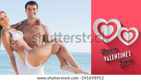 Man carrying his pretty girlfriend smiling at camera against happy valentines day - stock photo