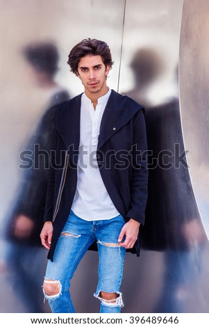 Man Casual Fashion. Portrait of American college student in New York. A handsome guy wearing fashionable long coat, jeans, standing against metal wall, looking at you. Filtered look with purple tint.  - stock photo