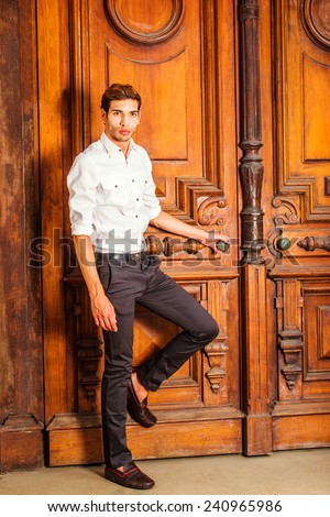 Man Casual Fashion. Wearing a white shirt, black pants, leather shoes, a young college student is standing by an old fashion style office door, a hand holding door knob, bending leg, waiting for you. - stock photo