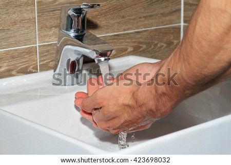 Man catches running water in his cupped hands. hands being washed under stream of pure water from tap