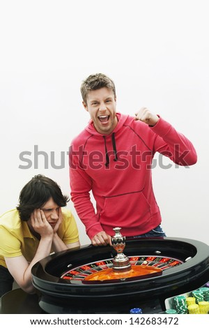Man Celebrating Gambling Win At Roulette Table - stock photo
