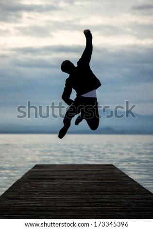 Man celebrating on empty pier jumping - stock photo