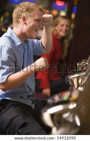 Man celebrating win at slot machine in casino - stock photo