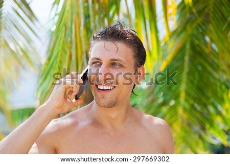 man cell phone call smile on beach summer vacation, green leaves palm tree background tourist ocean travel communication - stock photo