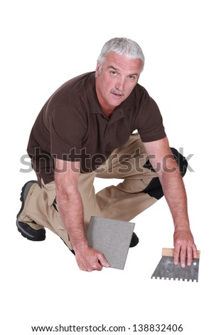 Man cementing tile to floor - stock photo