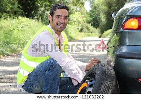 Man changing a tyre - stock photo
