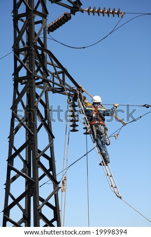 Man changing cable on high tension with nearly no security - stock photo