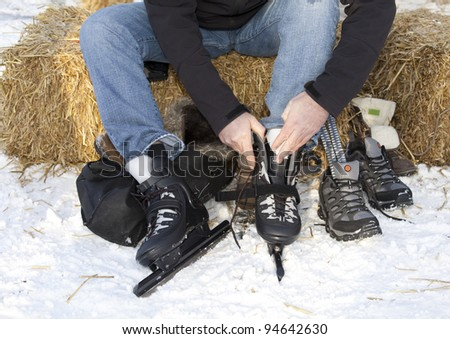 Man changing into speed ice skates sitting on straw in the snow - stock photo
