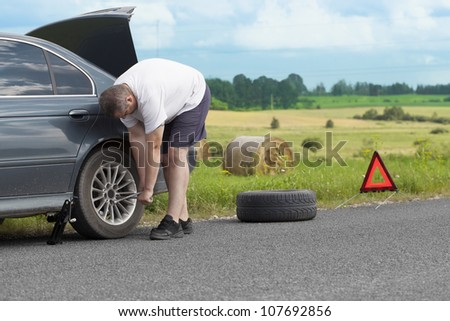 Man changing tire on the road - stock photo