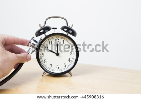 Man checking clock with a stethoscope - time concept