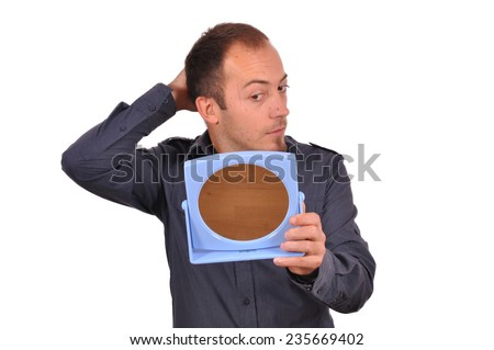 Man checking his hair loss in the mirror - stock photo