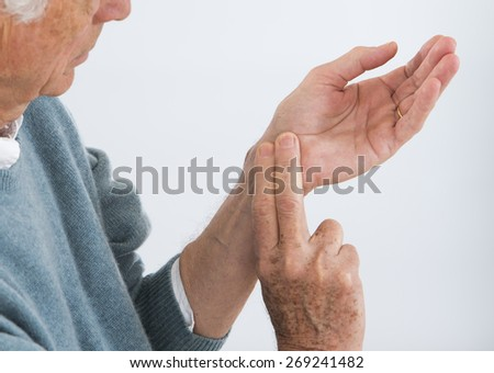 Man checking his pulse by pressing the wrist with fingers. - stock photo