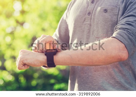 Man checking his smartwatch outside at sunset - stock photo