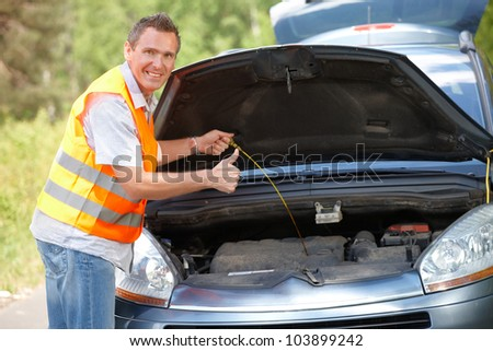 Man checking level of oil on a car engine dipstick, and showing ok sign
