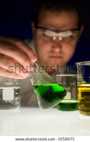 Man checking liquid in test tube. - stock photo