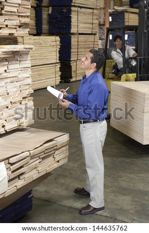 Man checking notes and laborer with forklift in the warehouse - stock photo