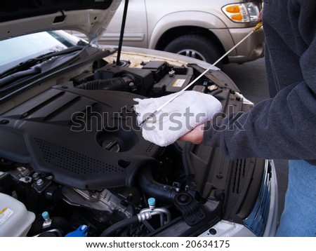 man checking oil level in car engine - stock photo