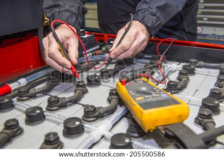 Man, checking the nodes of the battery pack of a forklift, using a multimeter - stock photo