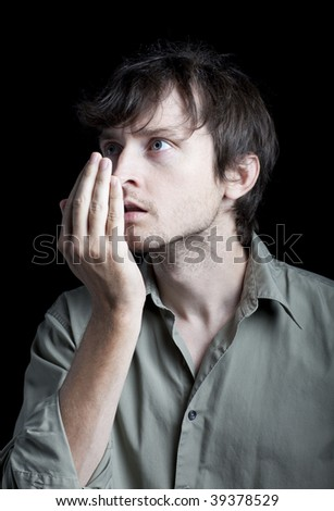 Man checks his breath by blowing in his hand and smelling - stock photo