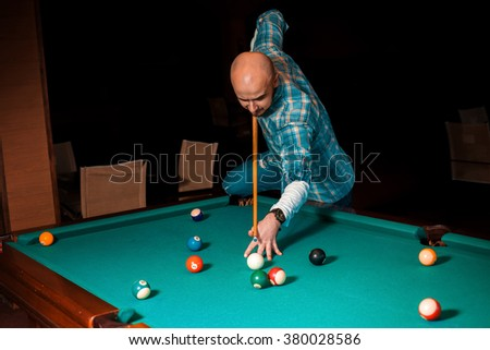 man chooses a difficult hit on pool billiards. American pool billiard. Pool billiard game. Billiard sport concept. - stock photo