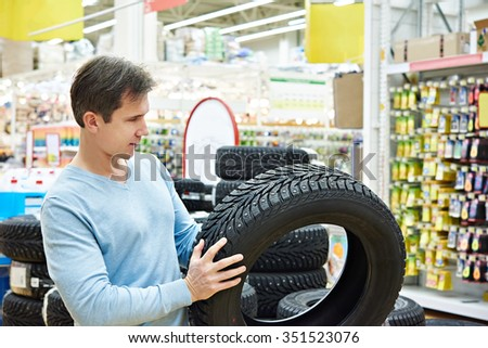 Man chooses a winter studded tires for a car in a supermarket - stock photo