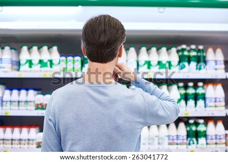 Man chooses dairy products in the store - stock photo