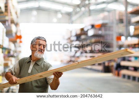 Man choosing and buying construction wood in a  DIY store for his DIY home re-modeling project - stock photo