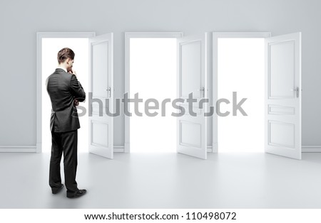 man choosing of three opened doors - stock photo