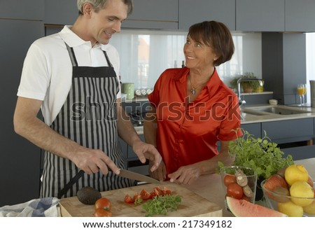 Man chopping vegetable on a cutting board with a woman standing beside him