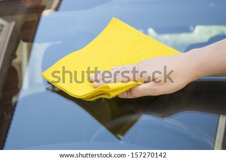 Man cleaning car glass front - stock photo