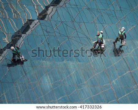 man cleaning slope glass building by rope access at height
