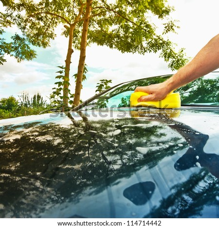 man cleaning the car in the sunny day - stock photo