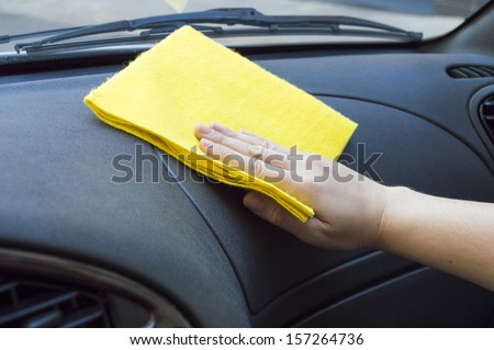 man cleaning the car interior with yellow cloth - stock photo