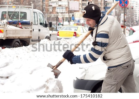 Man cleaning the snow with a shovel near his car - stock photo