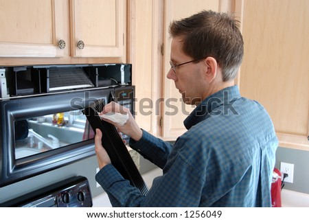 Man cleaning up after replacing the filter in a microwave in the kitchen of a  modern home. - stock photo