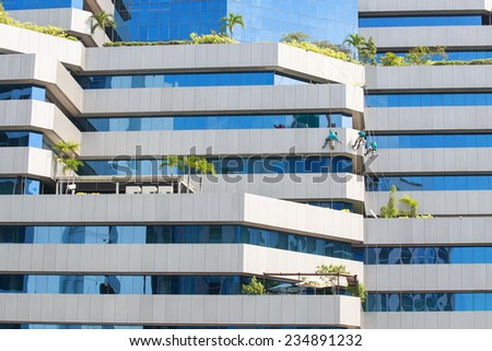 Man cleaning windows on a high rise building. - stock photo
