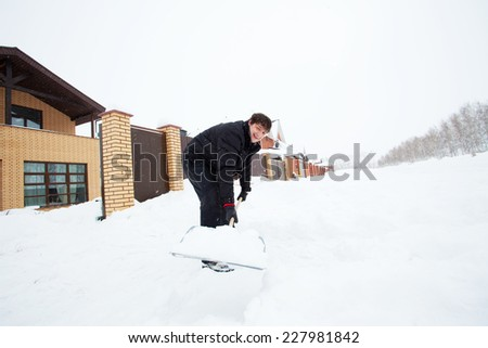 Man cleans snow shovel around the house - stock photo